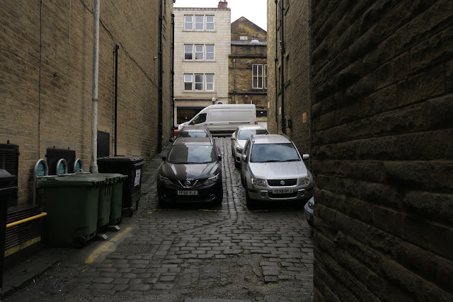 Cobbled street with cars and wheelie bins. Halifax. West Yorkshire.