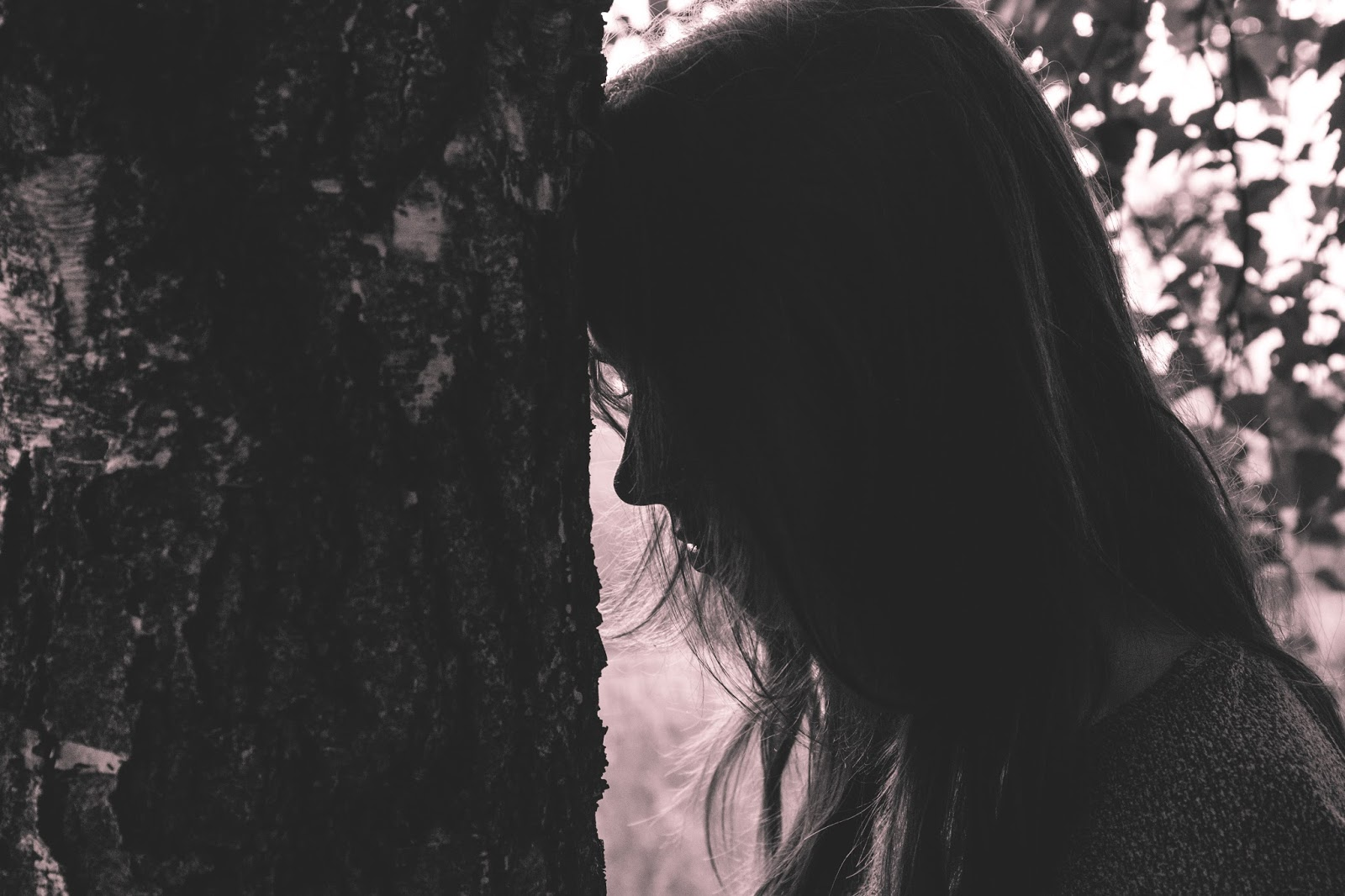 Woman looking sadly at a tree