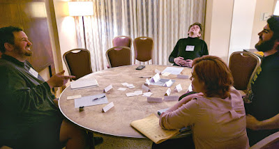 four people in a semi-circle around a table filled with index cards, paper, and writing instruments.