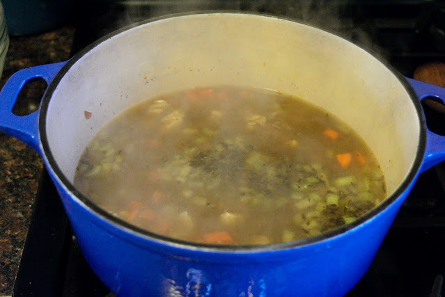 The chicken stock being added to the pot.