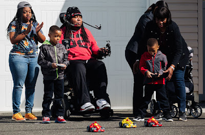 a family of five playing with r/c cars. Two of the cars are being controlled via remote control by two able bodied boys. The third is being controlled by a man in a wheelchair with a headset that has a pipe. Sipping and puffing into the pipe controls the r/c car.