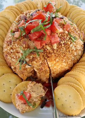 knife cutting into bacon bruschetta cheese ball with some spread on a cracker