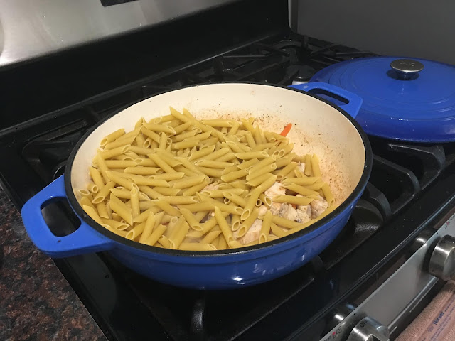 The uncooked pasta in the pan with the chicken and carrots.