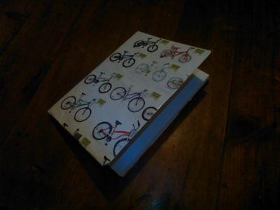 Cuaderno forrado con una hoja de revista vieja. El diseño de la tapa muestra imágenes de bicicletas