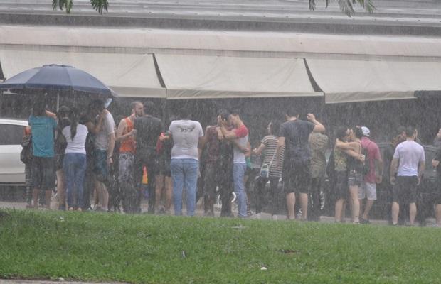 De baixo de chuva, grupo faz 'beijaço' na frente de bar em que casal sofreu homofobia