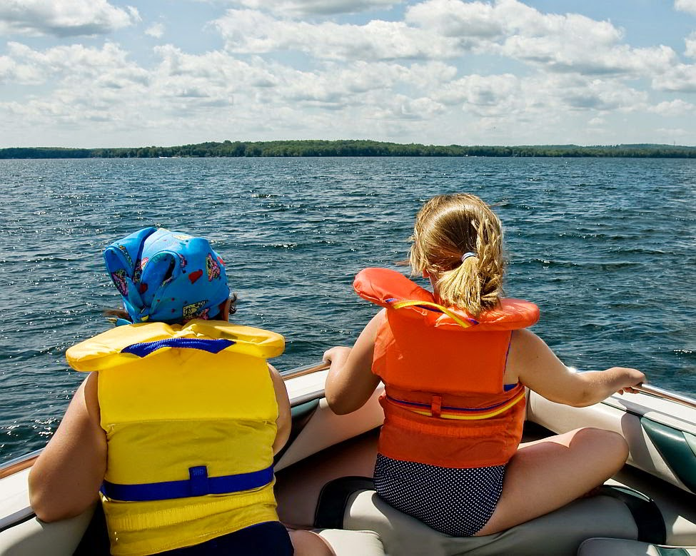 Two young girls wearing fitted kids life jackets.