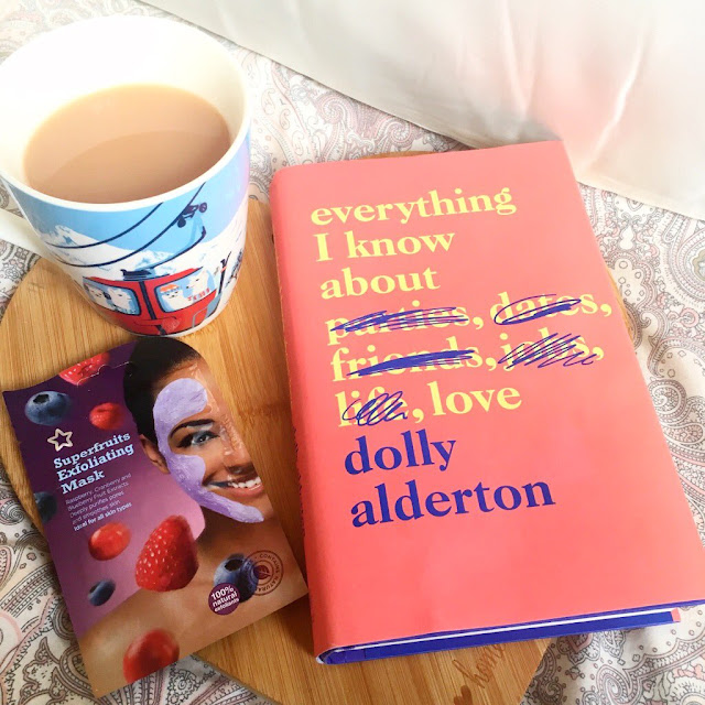 flatlay - silk pillowcase in the background, heart chopping board in front with book on top, face mask and cup of tea