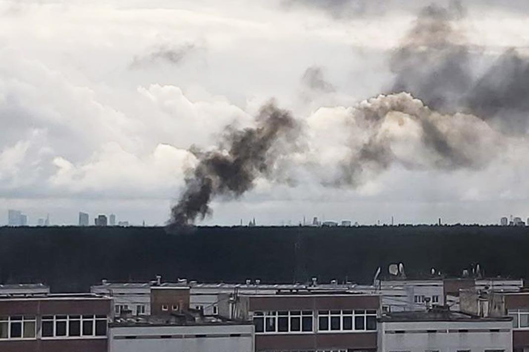Melni dūmi ceļas no meža masīva un ceļas virs daudzstāvu dzīvojamām mājām