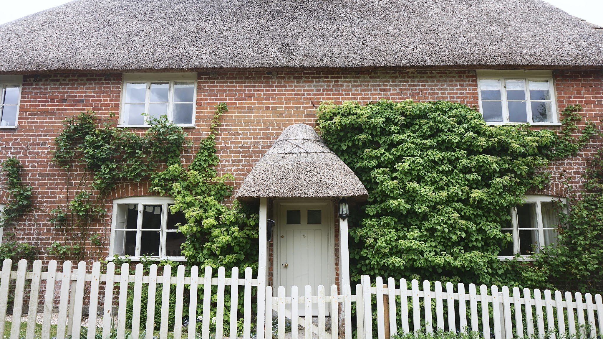 Two-storey brick cottage with a thatch roof, green wooden door and green picket fence