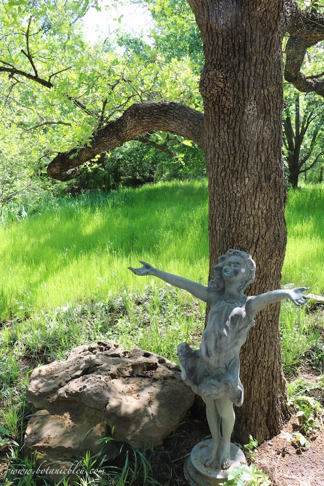 Spring grass meadow with girl statue and oak tree in backyard