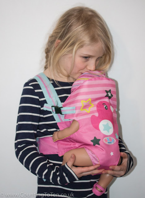 A girl kissing her BABY born dolls head while wearing her in a pin and blue BABY born carrier seat
