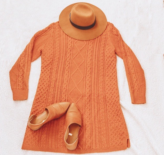 A flatlay of a brown panama hat, a burnt orange sweater dress and brown d'orsay flats.