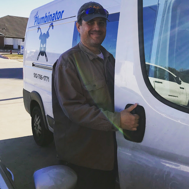 A medium build white man in his 40s stands, smiling as he opens the door of a white van with The Plumbinator logo of a skull and crosswrenches.