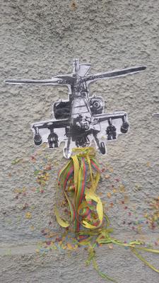 Detail: Der Krieg geht weiter - Installation - Hubschrauber werfen Luftschlangen und Konfetti ab - passend zu Fasching und Karneval
