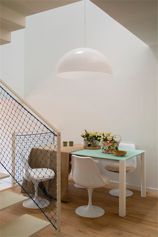 mesa con sobre de cristal traslucido y sillas tulip blancas chicanddeco