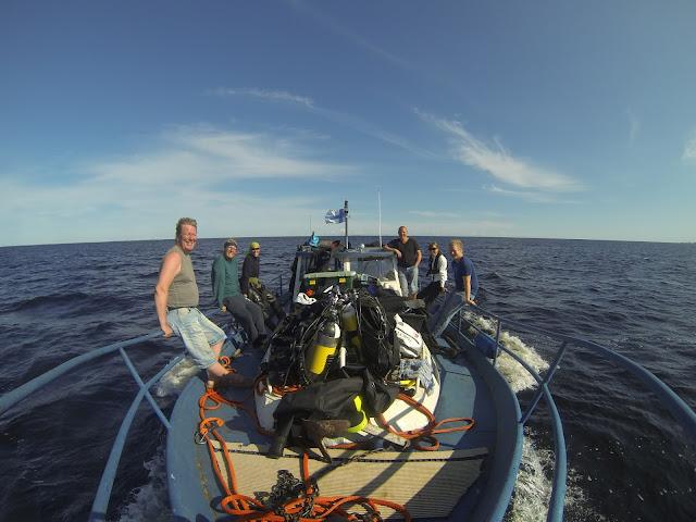 Vene täynnä sukelluskampetta. 6 ihmistä istuu veneen reunakaiteilla.