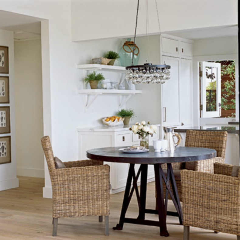 coastal wicker dining chairs surround the dark wood table an exposed