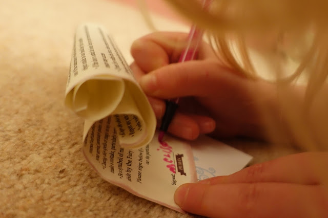 Close up of the fairy lease agreement and a young girl writing her name with a pink pen
