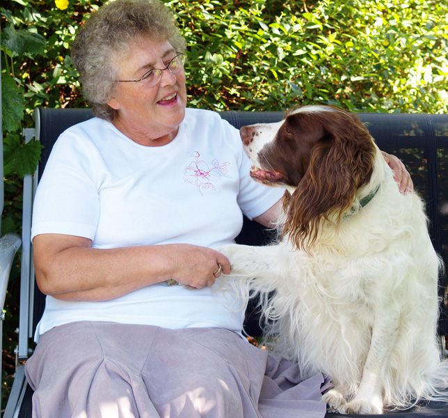 An older woman shakes paw with her spaniel