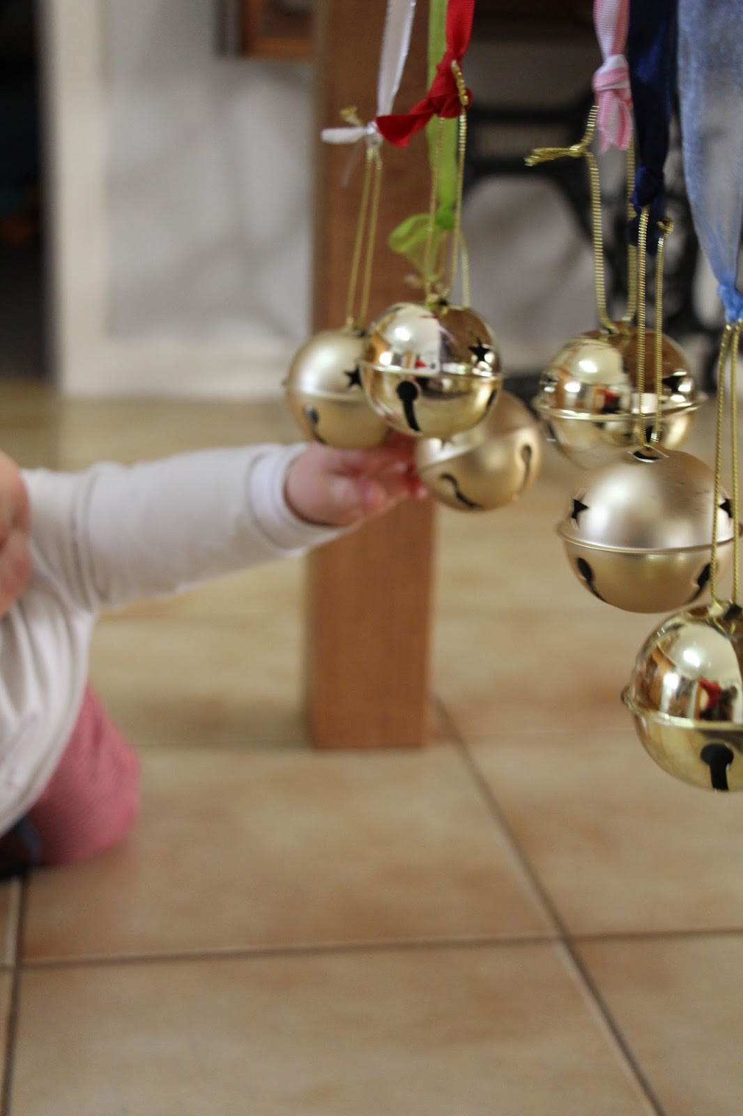 Baby touching bells hanging from a table