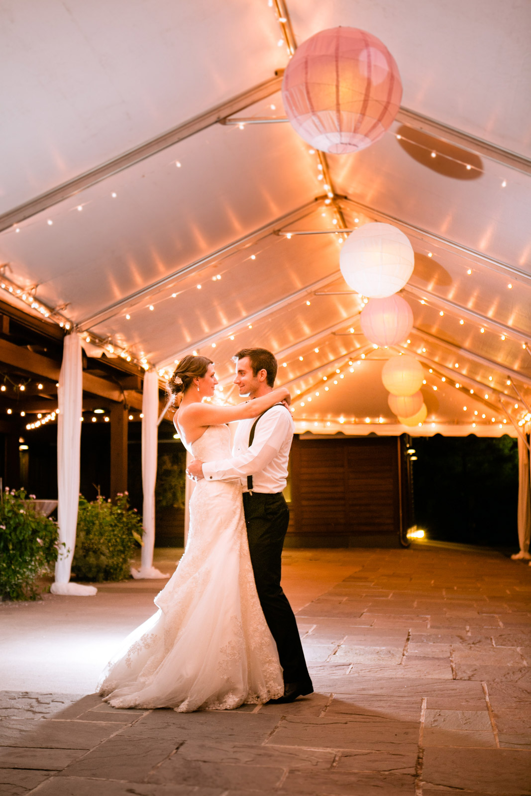 bride and groom stand under a lantern filled tent of sparkling lights at night