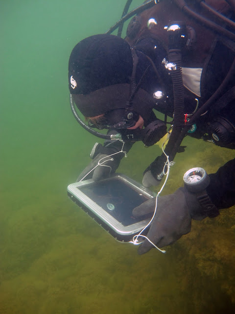 Sukeltaja käyttää tablettia veden alla