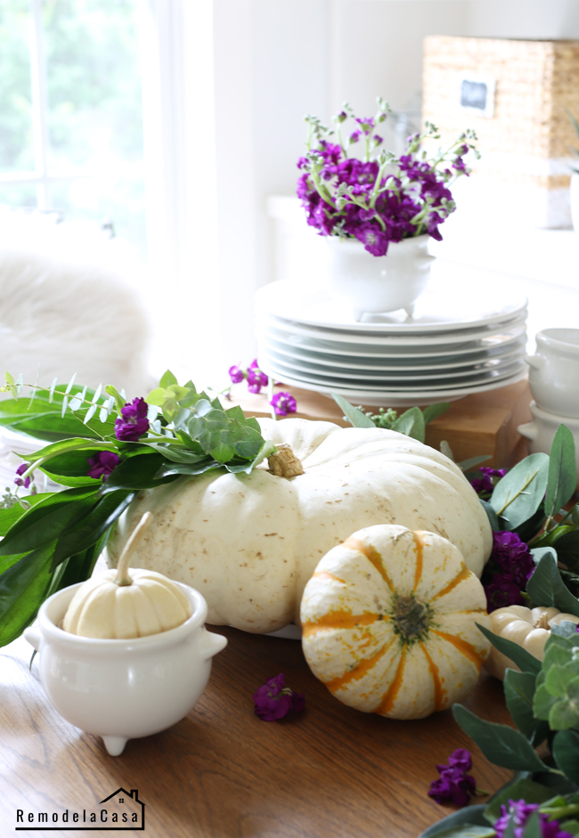White pumpkins, greenery and purple flowers on table