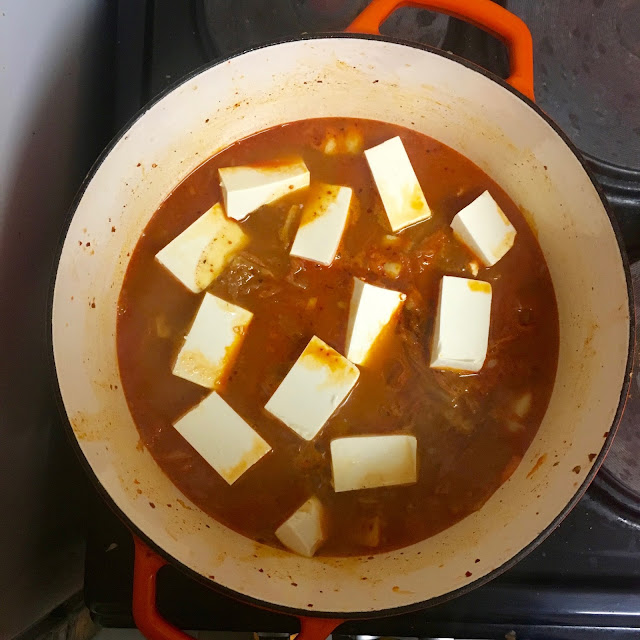 making kimchi jjigae in a casserole dish