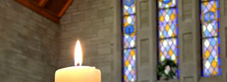 A candle lighting up a stained glass window