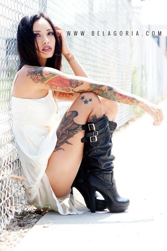 chica asiatica sentada en la calle, vemos tatuajes de tres estrellas en su pierna