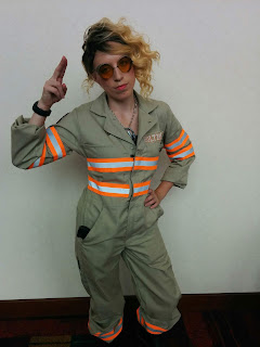A female dressed as Jillian Holtzmann from the 2016 reboot of Ghostbusters. She is wearing tinted safety goggles and the khaki coveralls with orange-and-white reflective stripes across the arms and torso.