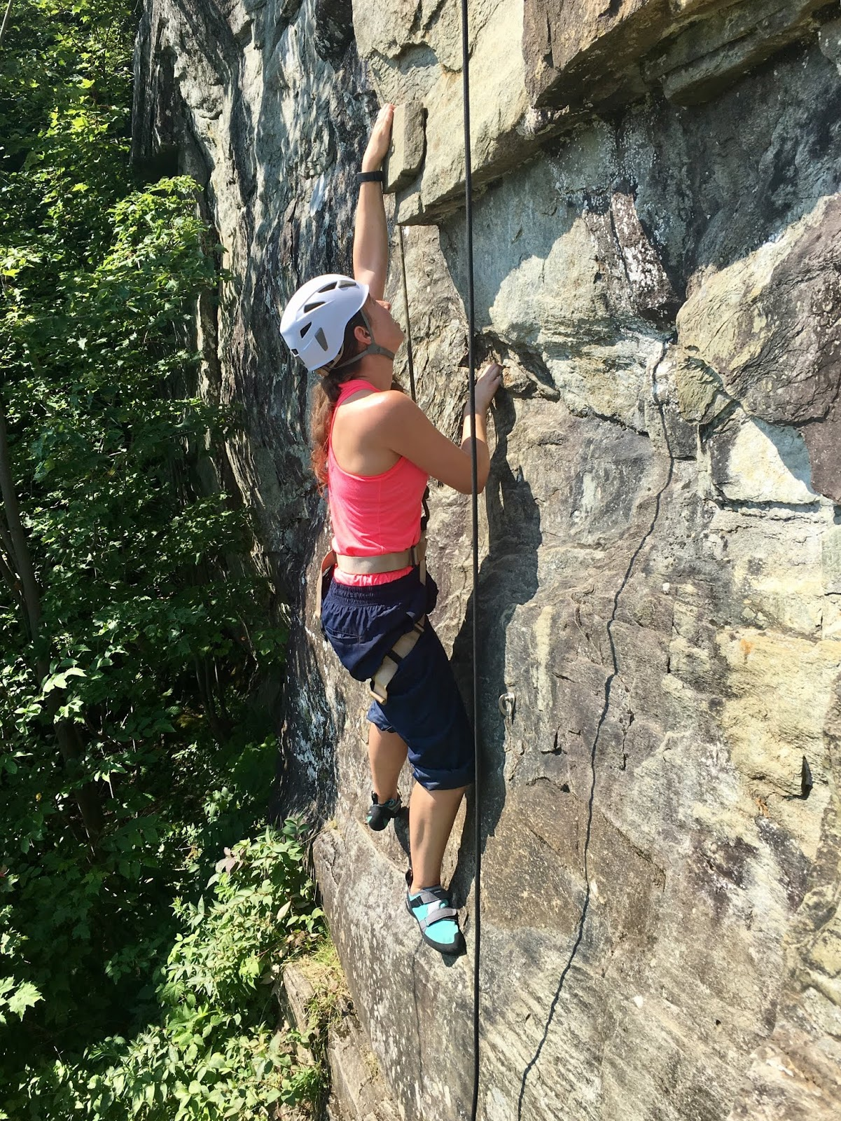 Capt. Rachel Antone climbs a cliff face in the woods near the Army Mountain Warfare School. She is wearing full climbing gear including a helmet and harness.