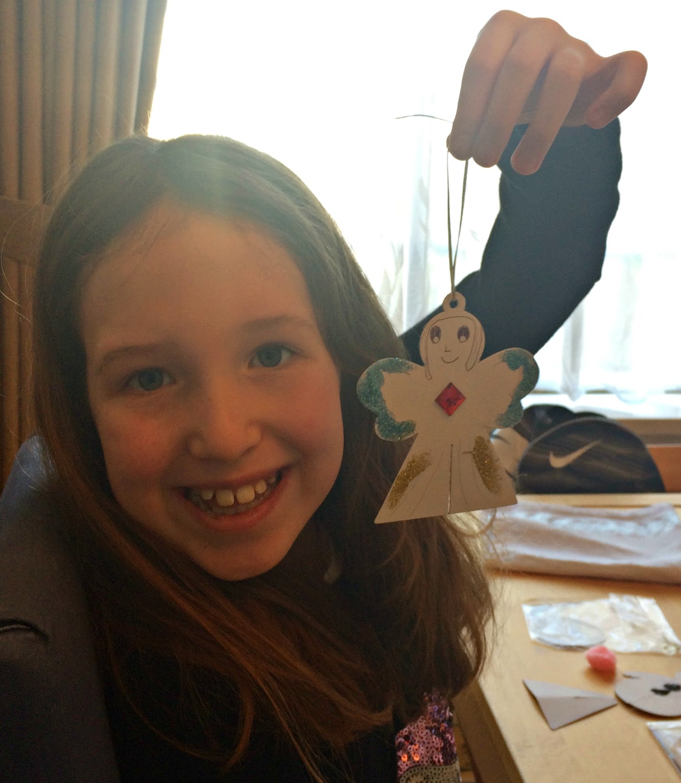 Caitlin holding up her Christmas angel decoration