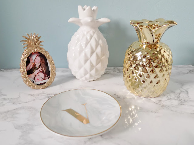 Gold pineapple homeware and marble background