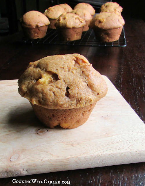 one pumpkin apple muffin close up with rest on a cooling rack in the background