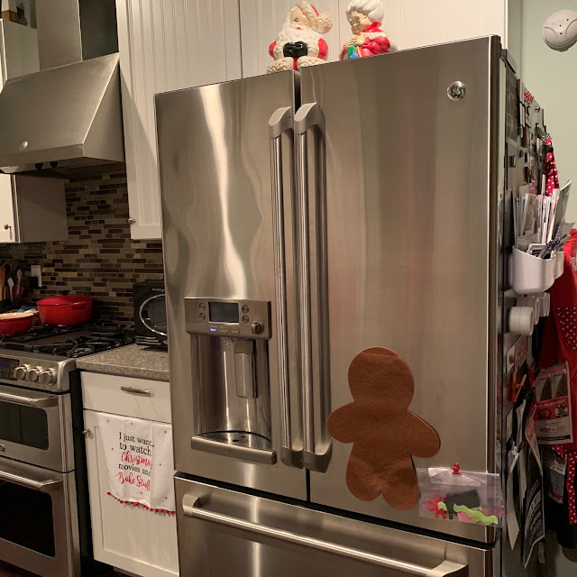 A photo of a kitchen, with Christmas decorations and a gingerbread man activity on the refrigerator