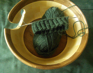 A cuff down sock on a circular needle. It is knit partway through the cuff in 2 by 2 ribbing.  The yarn is dark green, and needles, sock, and yarn, are resting in a wooden yarn bowl.