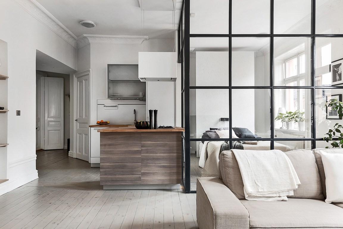 Bucătărie în mijlocul unei garsoniere și dormitor separat printr-un perete de sticlă