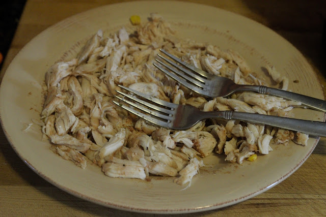 The chicken tenderloins, shredded, on a plate with forks on top of them.