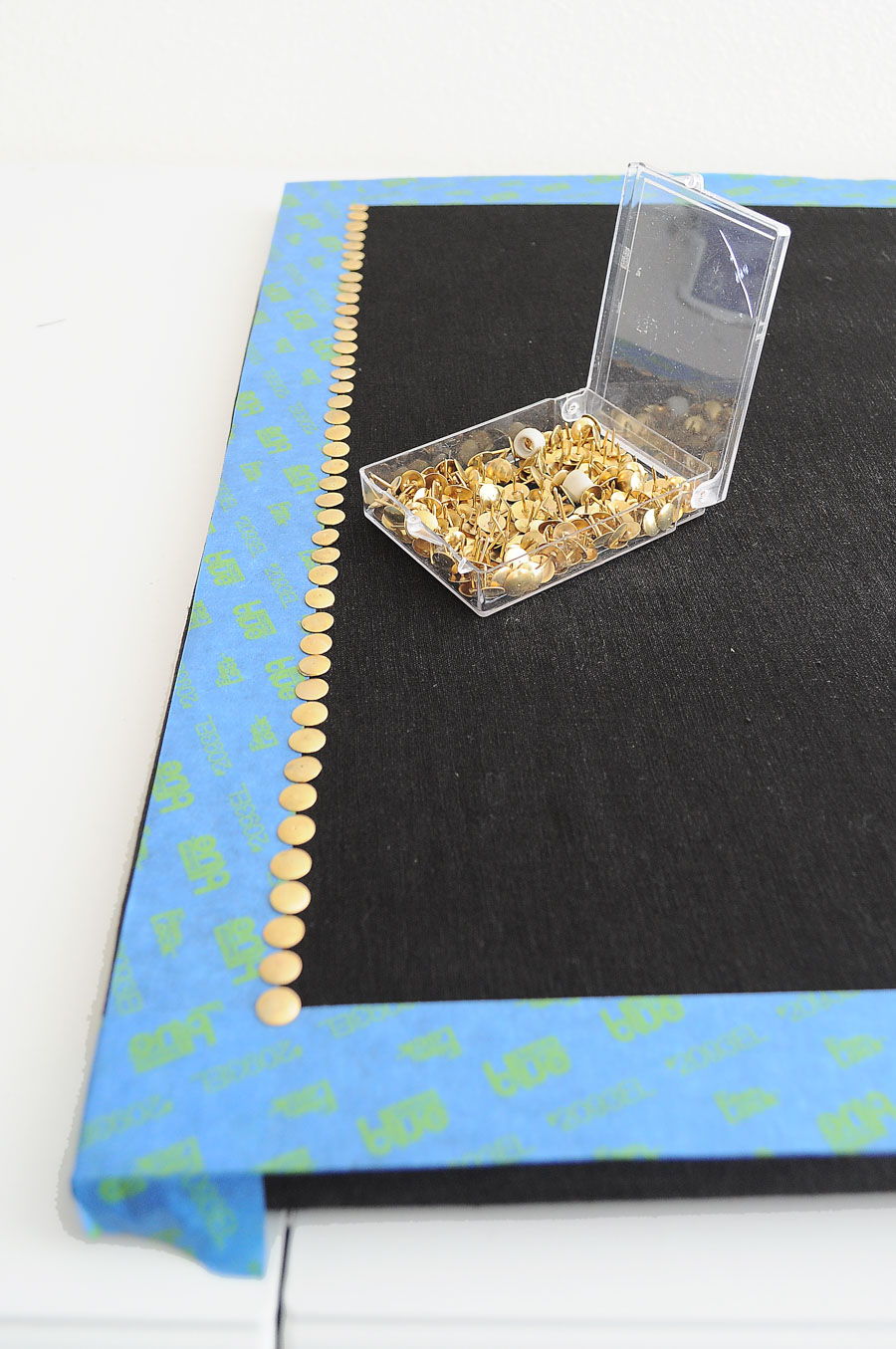 Use dollar store gold push pins or thumbtacks to create a faux nailhead border on a memo or cork board. What a great DIY idea!