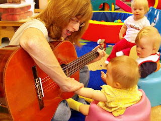 Teacher playing the guitar to children with communication problems