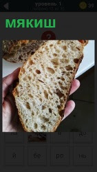 в руке человек держит хлебный мякиш, отрезанный от батона