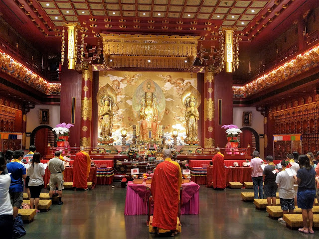Buddha Tooth Relic Temple interior with people praying