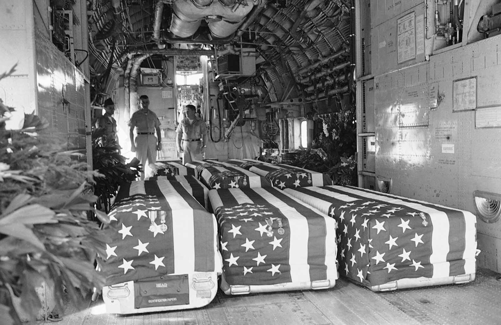 Flag-draped coffins of eight American Servicemen killed in attacks on U.S. military installations in South Vietnam, on February 7, are placed in transport plane at Saigon, February 9, 1965, for return flight to the United States. Funeral services were held at the Saigon Airport with U.S. Ambassador Maxwell D. Taylor and Vietnamese officials attending.