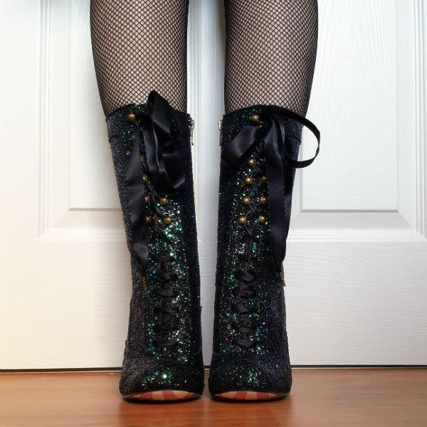 front facing legs wearing fishnet tights and glitter calf length boots