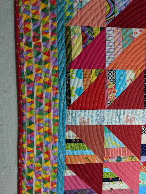 This shows part of the center, both borders, the pink binding, and the spiral quilting.