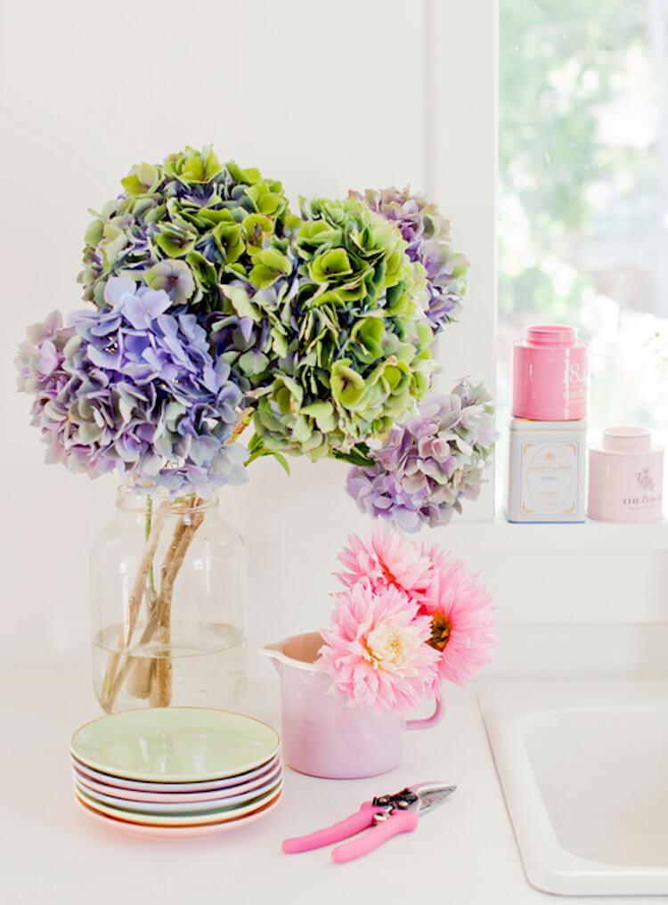 centro de flores frescas con tazas, platos en rosa suave