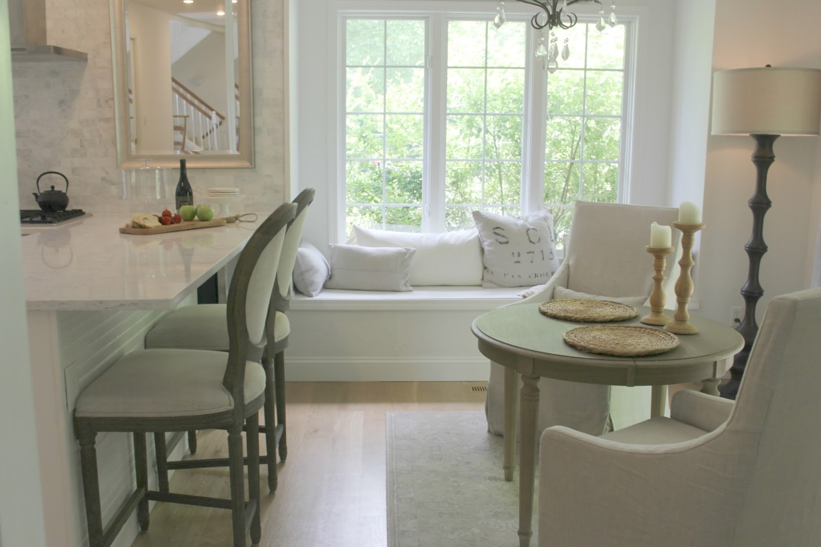 Serene white kitchen with Belgian linen and window seat by Hello Lovely Studio
