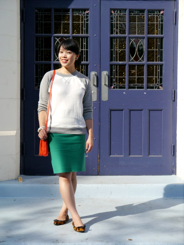 Vancouver blogger Lisa Wong of the blog Solo Lisa wears a cream-and-grey Forever 21 sweatshirt with a kelly green J. Crew pencil skirt. She finishes the look with a stack of gold and white enamel bracelets, pointy-toed leopard flats that have grosgrain bows on the vamp, and a little red crossbody bag.