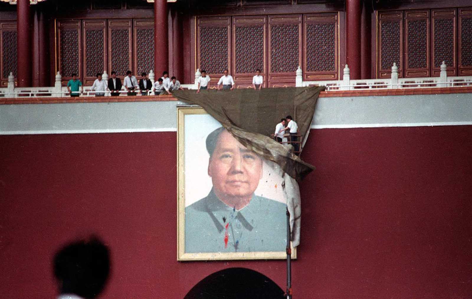 Workmen try to drape the portrait of Mao Tse-tung in Beijing's Tiananmen Square after it was pelted with paint, on May 23, 1989.